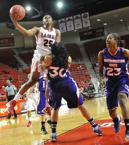 Lady Cardinal #25, Dominique Edwards, left, heads for the basket knocking down Lady Demon #30, Danielle Westerfield, right, as she drives towards the basket. The Lamar University Lady Cardinals tipped off at 5:30 p.m. against the Northwestern State Lady Demons Thursday night.  Dave Ryan/The Enterprise