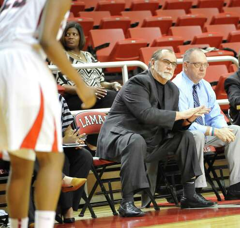 Head Coach Larry Tidwell, middle, gives a signal to one of his players during first half action. The Lamar University Lady Cardinals tipped off at 5:30 p.m. against the Northwestern State Lady Demons Thursday night.  Dave Ryan/The Enterprise Photo: Dave Ryan