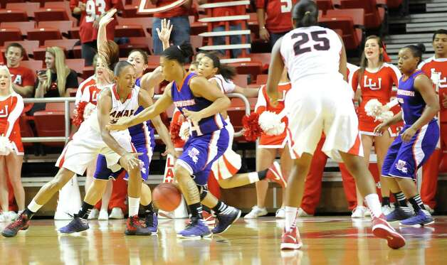 Lady Cardinal #5, Kalis Loyd, left, tries to grab the ball from Lady Demon #24, Jasmine Bradley during first half action. The Lamar University Lady Cardinals tipped off at 5:30 p.m. against the Northwestern State Lady Demons Thursday night.  Dave Ryan/The Enterprise Photo: Dave Ryan