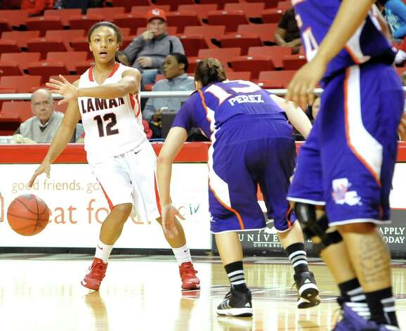 Lady Cardinal #12, Asia Booker, left, signals a teammate as she brings the ball down court around Lady Demon #13, Janelle Perezduring first half action. The Lamar University Lady Cardinals tipped off at 5:30 p.m. against the Northwestern State Lady Demons Thursday night.  Dave Ryan/The Enterprise Photo: Dave Ryan