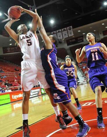 Lady Demon #1, Keisha Lee, middle, attempts to block the taller Lady Cardinal #5, Kalis Loyd, left, as she tries to take a shot during first half action. The Lamar University Lady Cardinals tipped off at 5:30 p.m. against the Northwestern State Lady Demons Thursday night.  Dave Ryan/The Enterprise