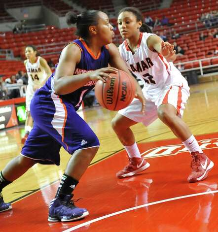 Lady Cardinal #12, Asia Booker, right, attempts to block Lady Demon #1, Keisha Lee, left, as she drives for the basket.  The Lamar University Lady Cardinals tipped off at 5:30 p.m. against the Northwestern State Lady Demons Thursday night.  Dave Ryan/The Enterprise