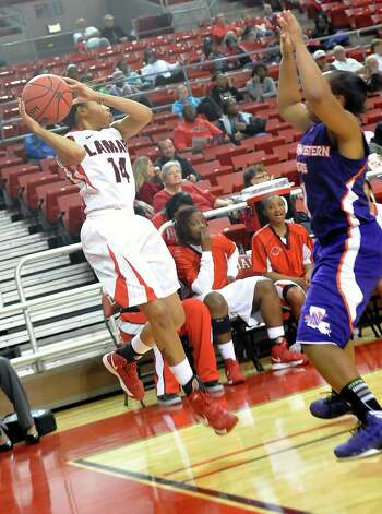 Lady Cardinal #14, Carenn, Baylor left, tries to throw a pass before going out of bounds during first  half action. The Lamar University Lady Cardinals tipped off at 5:30 p.m. against the Northwestern State Lady Demons Thursday night.  Dave Ryan/The Enterprise Photo: Dave Ryan