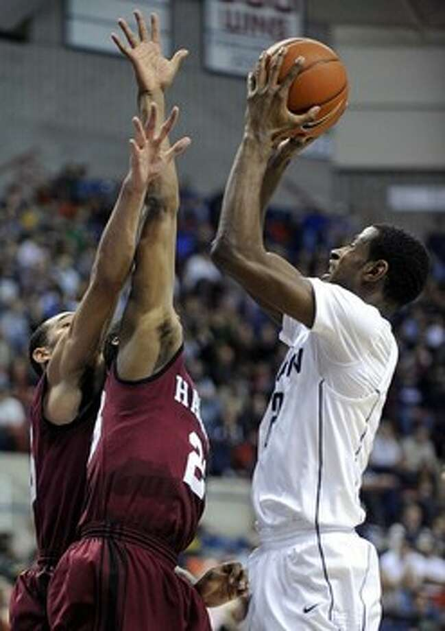 Connecticut's DeAndre Daniels, right, shoots over Harvard's Christian Webster, left, and Wesley Saunders during the second half of an NCAA college basketball game in Storrs, Conn., Friday, Dec. 7, 2012. Daniels scored a game-high 23 points during his team's 57-49 victory. Photo: Fred Beckham, AP / FR153656 AP