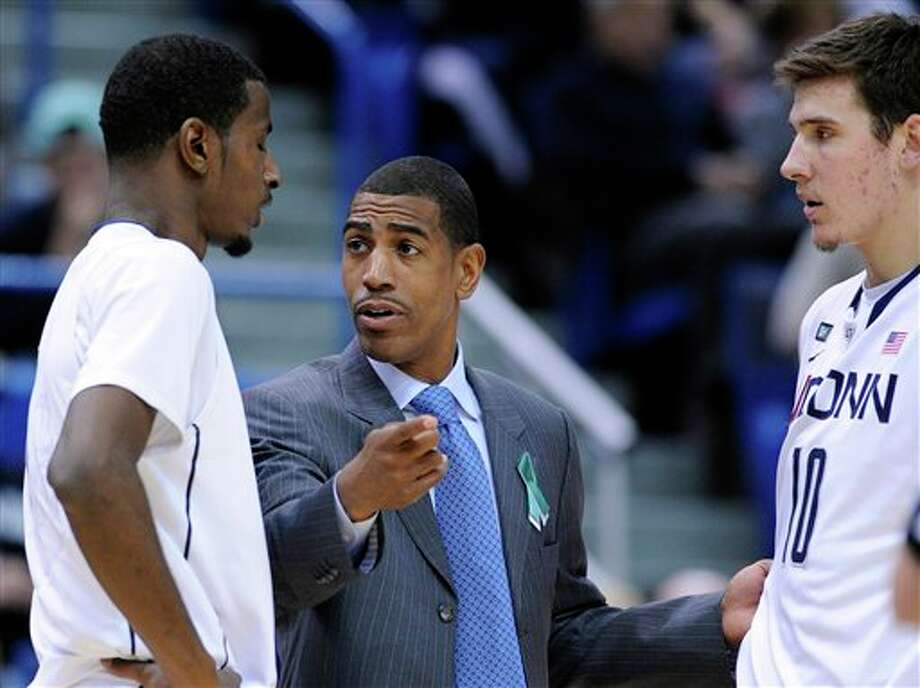 Connecticut coach Kevin Ollie, center, speaks DeAndre Daniels, left and Tyler Olander during the second half of an NCAA college basketball game in Hartford, Conn., Friday, Dec. 21, 2012. Connecticut won the game 88-73. Photo: Fred Beckham, AP / FR153656 AP