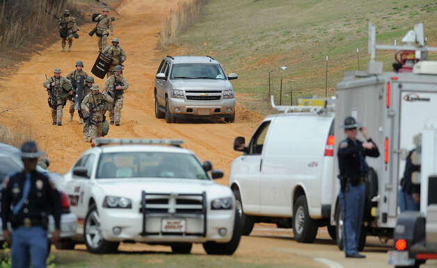 Heavily armed men move away from the suspects home at the scene of a Dale County hostage scene in Midland City, Ala. on Wednesday Jan. 30, 2013. Authorities