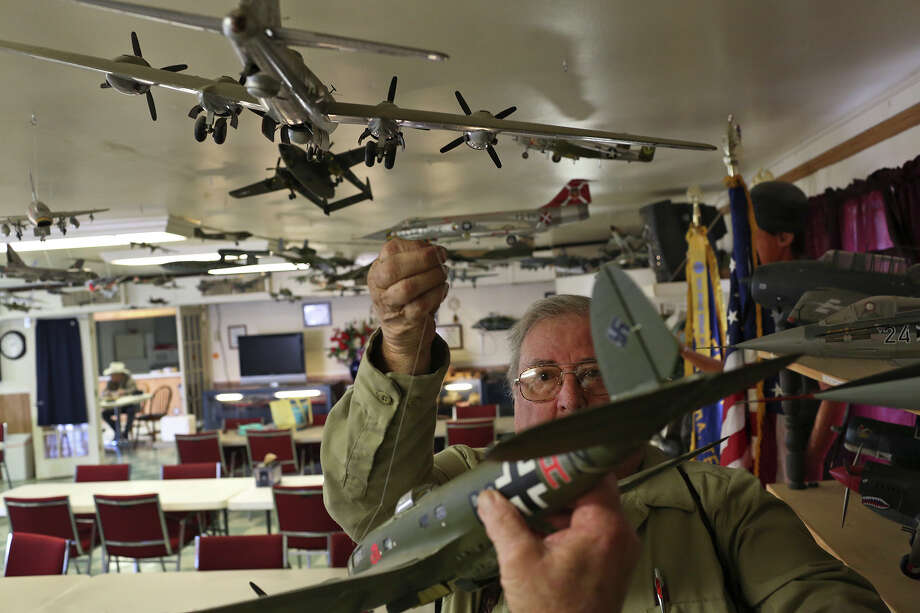 Rusty Landry hangs a model plane from the ceiling after fixing it, one that he built, which is amid the 147 he donated on display at American Legion Post 157 in Bandera on Friday, Feb. 1, 2013. Photo: Lisa Krantz, San Antonio Express-News / © 2012 San Antonio Express-News