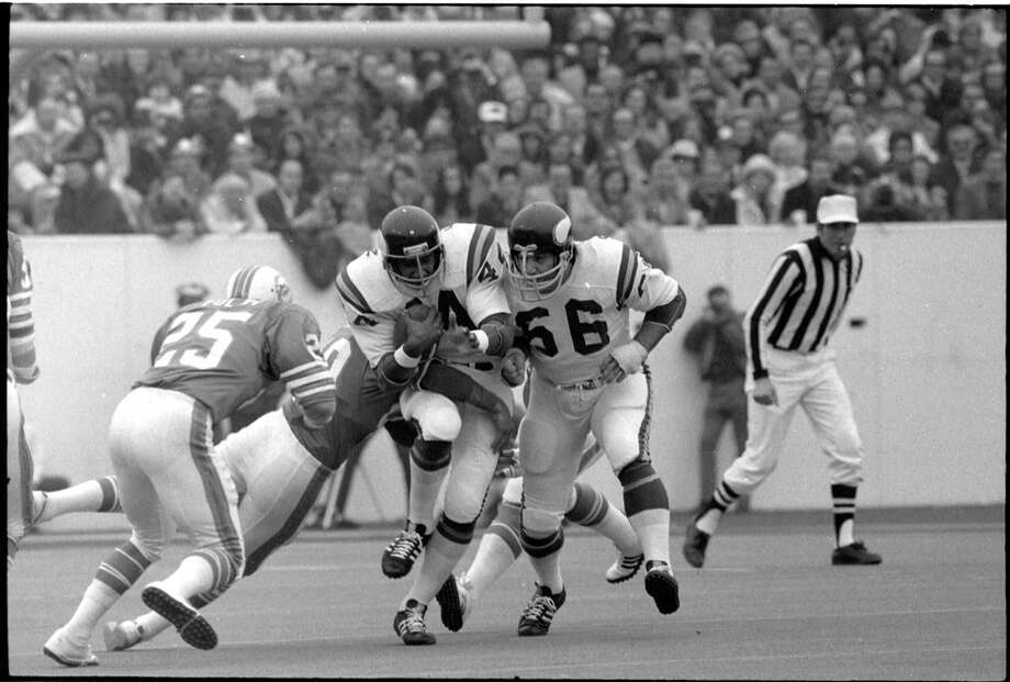 Dolphins cornerback Tim Foley (25) comes in to try to tackle Vikings fullback Chuck Foreman (44). Photo: Darrell Davidson, Houston Chronicle / Houston Chronicle