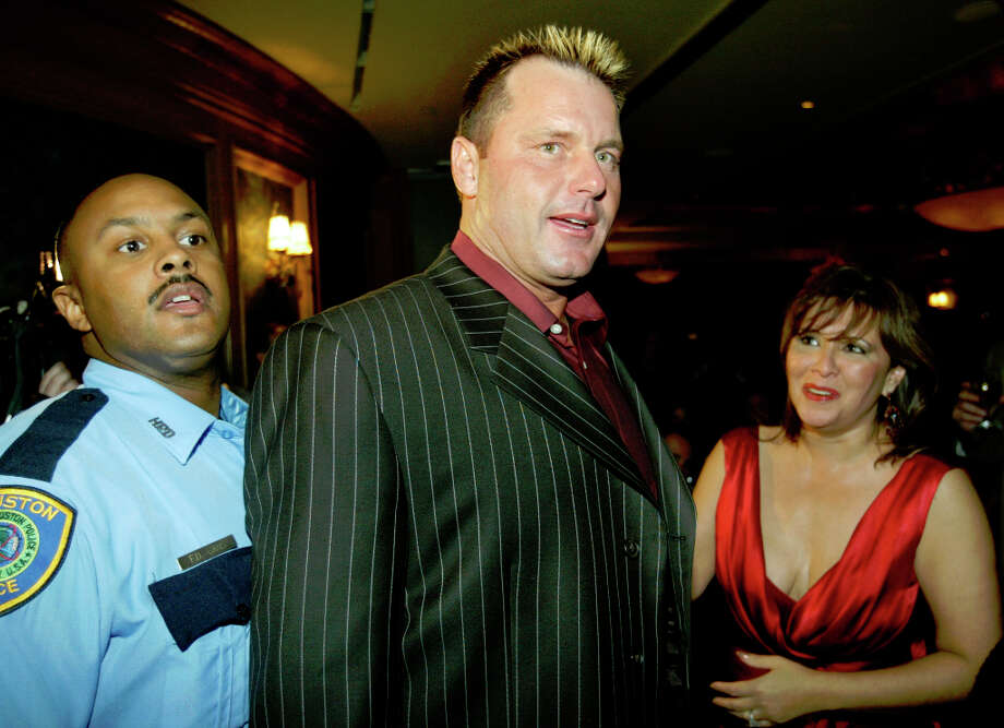 With the aid of Debbie Festari, right, and an unidentified police officer, Roger Clemens makes his way through the crowd as he enters the NFL Fashion at the Aquarium restaurant. Photo: Andrew Innerarity, Houston Chronicle / Houston Chronicle