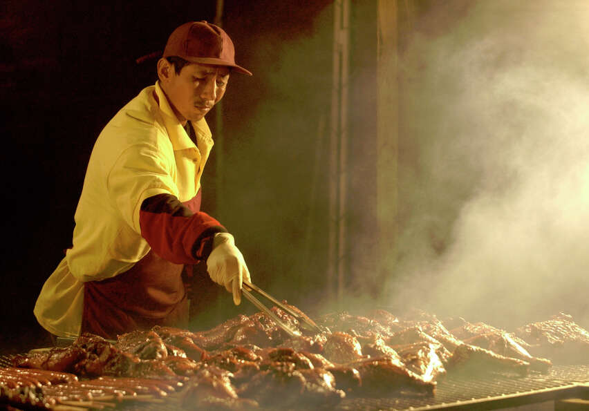 Juan Hernandez is surrounded by smoke while cooking smoked turkey legs at a food booth named Juicy's