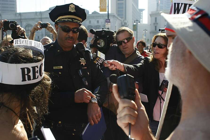 A San Francisco Police officer gives the protesters 15 minutes to leave city hall or face arrest on