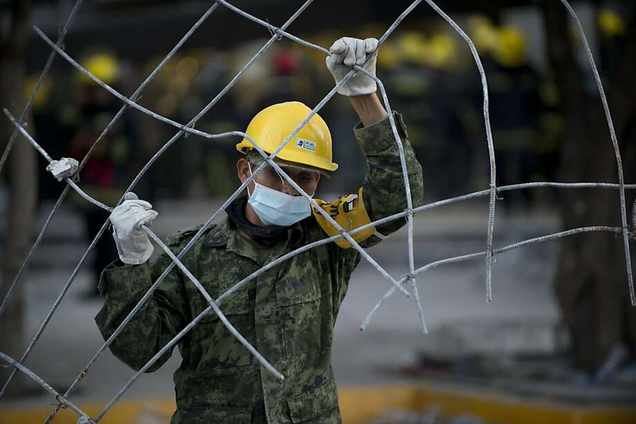A Mexican soldier removes debris from the headquarters of the state-owned Mexican oil giant Pemex in Mexico City on February 1, 2013, following a blast inside the building. An explosion rocked the skyscraper, leaving up to now 25 dead and 100 injured, as a plume of black smoke billowed from the 54-floor tower, according to official sources.  AFP PHOTO/ YURI CORTEZYURI CORTEZ/AFP/Getty Images Photo: Yuri Cortez, AFP/Getty Images