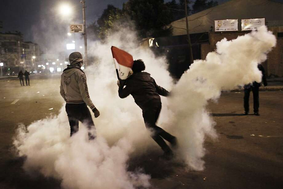 An Egyptian protester throws a tear gas canister back at security forces during clashes outside the presidential palace in Cairo. One man died when he was shot in the chest and forehead. Photo: Ed Giles, Getty Images