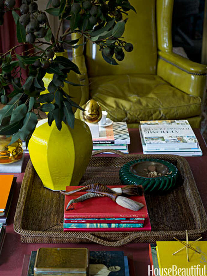 "Layer With a TrayIn a Lattingtown, New York, house, designer Meg Braff added a tray to a coffee table in the den. Large coffee tables ""don't feel so massive when you layer on a tray. It breaks up the surface,"" she says. Photo: James Merrell / © James Merrell"