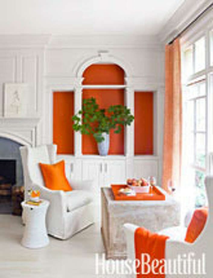 "Add Unexpected ColorIf you don't want to hang a piece of art, color in an unusual place can make a statement, such as in this Atlanta living room. Designer Kay Douglass painted an empty bookcase orange, which sets off the Palladian details. ""You notice it right away, don't you?"" she says. ""It almost becomes an art piece and helps make the room, instead of being just a place to store things. One of the biggest design mistakes people make is cluttering their world with too many things."" Photo: Eric Piasecki / © 2012 Eric Piasecki"