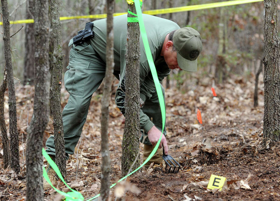 A Texas Ranger combs the ground Thursday in an area where several bones and a man's skull were discovered. Found north of Jasper on Tuesday, the skull has yet to be identified, but an investigation is underway. It is unknown at this point if the other bones are human.  Photo taken Thursday, January 23, 2013 Guiseppe Barranco/The Enterprise Photo: Guiseppe Barranco, STAFF PHOTOGRAPHER / The Beaumont Enterprise