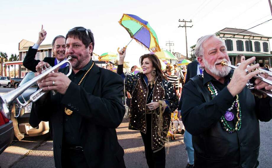 Jim and Dancie Ware follow the Pizaz Dixieland Band on a Mardi Gras procession along 25th Street en route to the Tremont Hotel where they will be presented with the George P. Mitchell Mardi Gras Award Friday, Feb. 1, 2013, in Galveston. Photo: Nick De La Torre, Chronicle / © 2010 Houston Chronicle