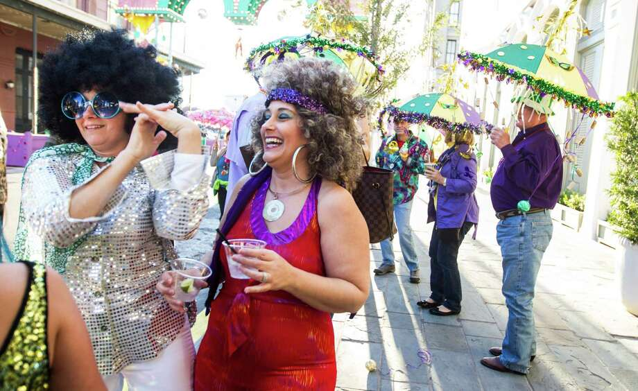 Charlene Doherty, left, of Akron, Ohio, goofs around with Eileen Donlon, of Galveston as they attend a Mardi Gras ceremony outside the Tremont Hotel Friday, Feb. 1, 2013, in Galveston. Jim and Dancie Ware were given the George P. Mitchell Mardi Gras Award. during the ceremony. Photo: Nick De La Torre, Chronicle / © 2010 Houston Chronicle