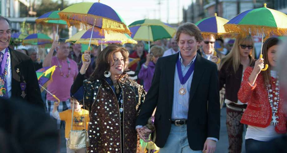 Dancie Ware, left, and her son Carter Ware follow the Pizaz Dixieland Band on a Mardi Gras procession along 25th Street en route to the Tremont Hotel where Dancie will be presented with the George P. Mitchell Mardi Gras Award Friday, Feb. 1, 2013, in Galveston. Photo: Nick De La Torre, Chronicle / © 2010 Houston Chronicle