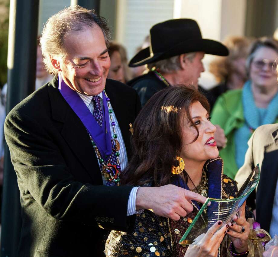 Jim and Dancie Ware look at a gift they received after being awarded the George P. Mitchell Mardi Gras Award Friday, Feb. 1, 2013, outside the Tremont Hotel in Galveston. Photo: Nick De La Torre, Chronicle / © 2010 Houston Chronicle
