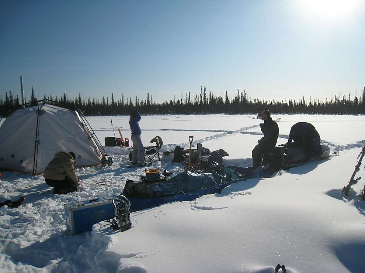 Lin Liu (left), Kristina Keating (center), and Bill Cable enjoy a brief warm part of the afternoon while starting to pack up the instruments after finishing their measurements on the last day at Caribou Lake, near Fairbanks, AK.