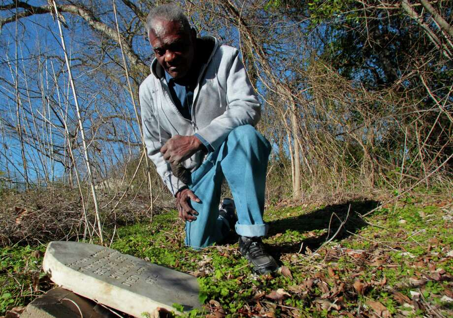 Eddie Harrison, a former municipal judge in Brenham, examines a toppled tombstone at the Camp Town Cemetery. Photo: Billy Smith II, Staff