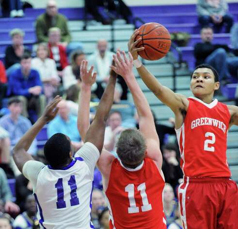 At right, CJ Byrd of Greenwich goes high to grab a rebound over teammate Alex McMurray # 11, center, and Guyveson Cassamajor #11 of Westhill during the boys high school basketball game between Westhill High School and Greenwich High School at Westhill in Stamford, Friday night, Feb. 1, 2013. Photo: Bob Luckey / Greenwich Time