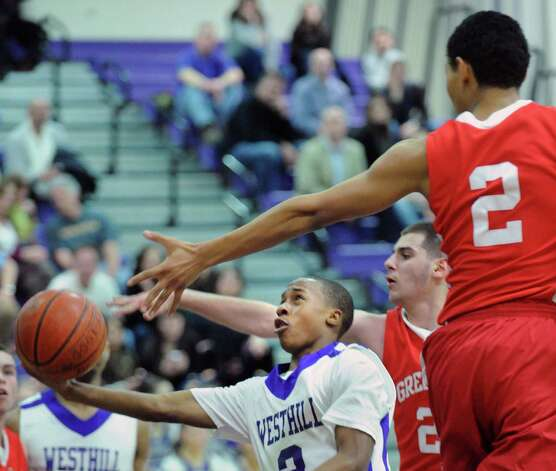 At left, C.J. Donaldson # 3 of Westhill gets past Jim Djema # 20 of Greenwich and CJ Byrd,# 2, also of Greenwich, to score on a layup durng the boys high school basketball game between Westhill High School and Greenwich High School at Westhill in Stamford, Friday night, Feb. 1, 2013. Photo: Bob Luckey / Greenwich Time