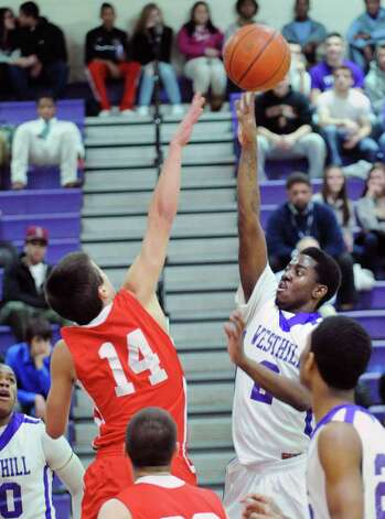 At left, Thomas Baietto # 14 of Greenwich attempts to block the shot of Westhill's Terrell Middleton # 2 who scores on the play during the boys high school basketball game between Westhill High School and Greenwich High School at Westhill in Stamford, Friday night, Feb. 1, 2013. Photo: Bob Luckey / Greenwich Time