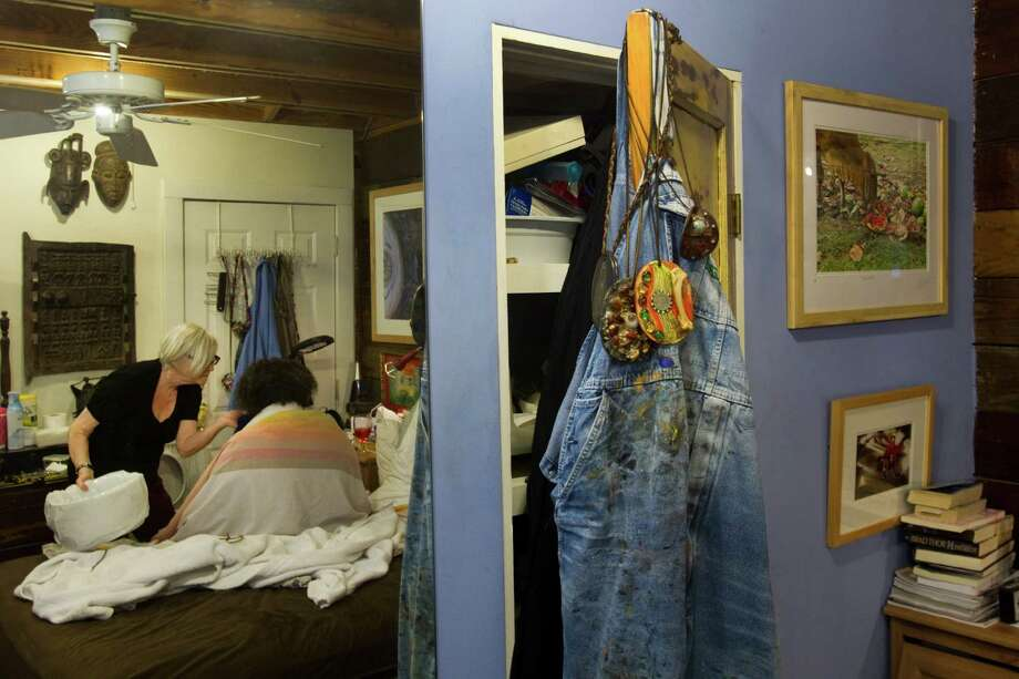 Bert Long's paint-stained overalls and pendents hang from a closet door while his wife, Joan Batson, cares for the ailing artist Monday, Jan. 28, 2013, in Houston. Photo: Brett Coomer, Houston Chronicle / © 2013 Houston Chronicle