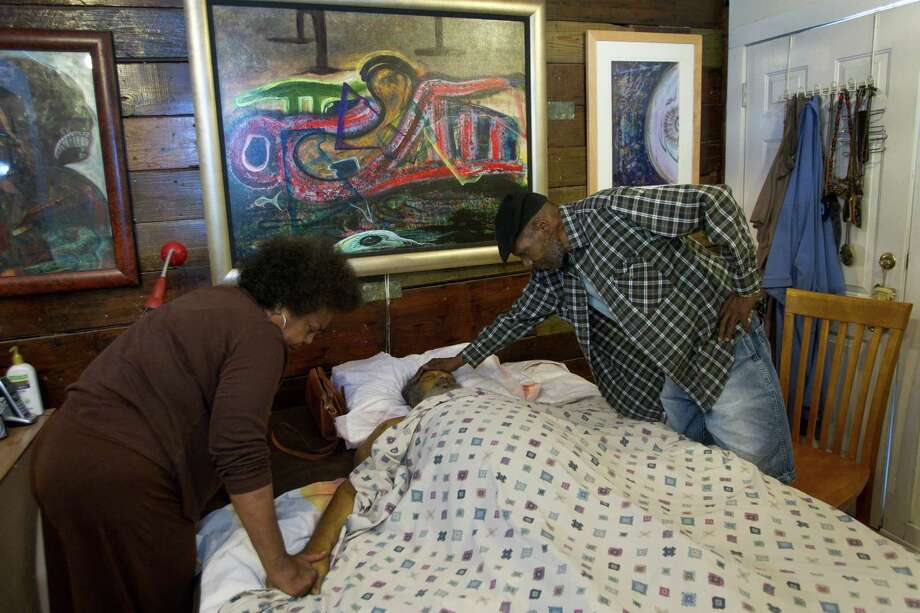 Violet White, sister of artist Bert Long, and her husband, Clifton White, mourn over the body of the artist shortly after he died Friday, Feb. 1, 2013, in Houston. Long, a renowned Houston artist, died in his 5th Ward home with his family at his bedside. Photo: Brett Coomer, Houston Chronicle / © 2013 Houston Chronicle