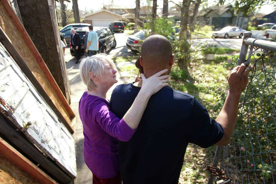 Joan Batson, wife of artist Bert Long, comforts Bertran Long III as he watches his father's body being taken from the home Friday, Feb. 1, 2013, in Houston. Photo: Brett Coomer, Houston Chronicle / © 2013 Houston Chronicle