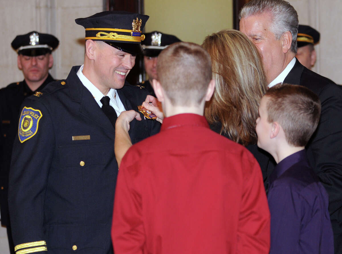 Commander Erin Commerford gets his new badge pinned on him by his wife Stephanie during a swearing in ceremony of nine newly promoted members of the Albany Police Department at City Hall Friday Feb. 1, 2013 in Albany, N.Y. His sons Ryan and Jack along with Mayor Jerry Jennings look on. (Lori Van Buren / Times Union)