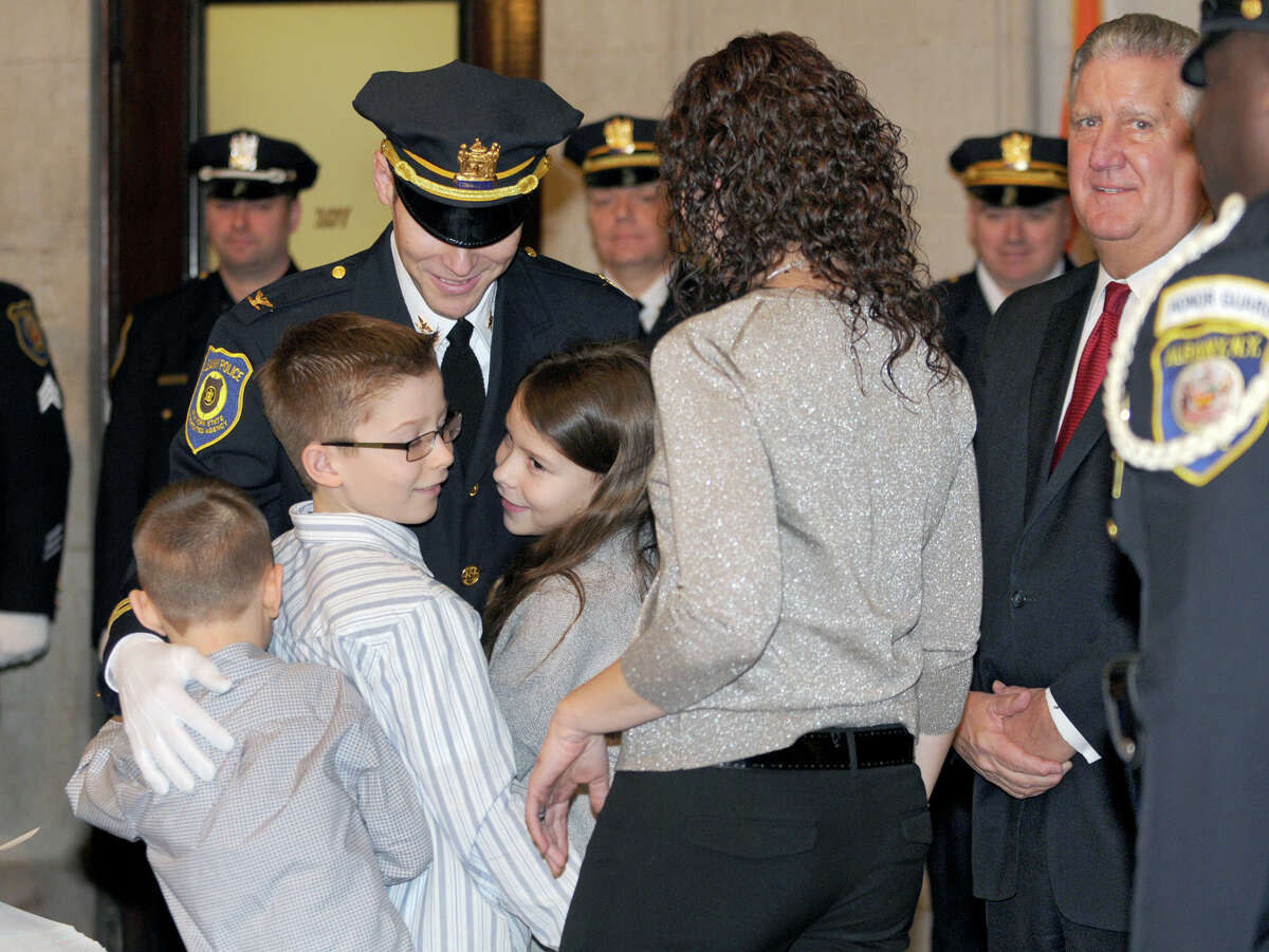 Commander Jeffrey Roberts gets hugs from his family (from left) Brady, 6, Max, 10, Shay, 9, and his wife Christine during a promotion ceremony at City Hall Friday Feb. 1, 2013 in Albany, N.Y. Mayor Jennings, right, and Chief Krokoff swore in nine newly promoted members of the Albany Police Department. (Lori Van Buren / Times Union)