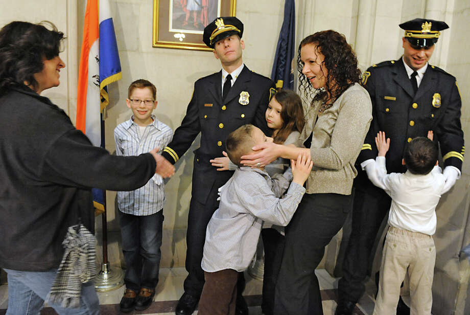 Amiee Devane-Forster, left, of Slingerlands congratulates her friend Commander Jeffrey Roberts on his promotion at City Hall Friday Feb. 1, 2013 in Albany, N.Y. Roberts is surrounded by his family from left, Max, 10, Brady, 6, Shay, 9, and his wife Christine. On right is Commander Robert Sears with his son Brady, 6. Mayor Jennings and Chief Krokoff swore in nine newly promoted members of the Albany Police Department.  (Lori Van Buren / Times Union) Photo: Lori Van Buren