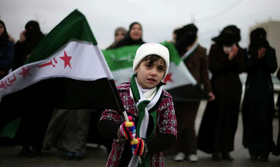 "A girl waves the revolutionary Syrian flag during a protest against President Bashar Assad in front of the Syrian embassy to commemorate the 31st anniversary of the 1982 Hama massacre, in the era of Hafez Assad, in Amman, Jordan, Friday, Feb. 1, 2013. The Arabic writing on the flag reads ""free Syria."" (AP Photo/Mohammad Hannon) Photo: Mohammad Hannon"
