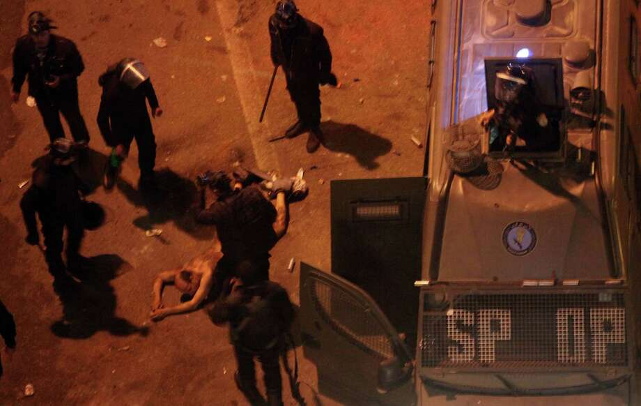 Egyptian riot police beat a man, after stripping him, and before dragging him into a police van, during clashes next to the presidential palace in Cairo, Egypt, Friday, Feb. 1, 2013. Protesters denouncing Egypt's Islamist president hurled stones and firebombs through the gates of his palace gates on Friday, clashing with security forces who fired tear gas and water cannons, as more than a week of political violence came to Mohammed Morsi's symbolic doorstep for the first time. (AP Photo/Khalil Hamra) Photo: Khalil Hamra