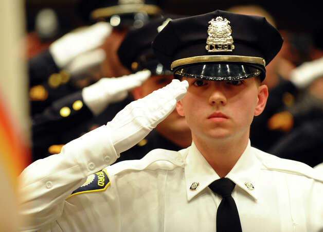 New police officer Matthew Ackerman salutes the flag during a graduation ceremony at Bridgeport City Hall's Council Chambers in Bridgeport, Conn. on Friday February 1, 2013. Photo: Christian Abraham / Connecticut Post