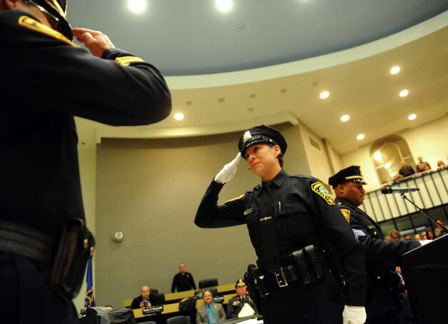 New Norwalk police officer, Kelly Hollister, from the Bridgeport Police Academy, salutes Bridgeport Police Chief Joseph Gaudett, during the graduation ceremony at Bridgeport City Hall's Council Chambers in Bridgeport, Conn. on Friday February 1, 2013. Photo: Christian Abraham / Connecticut Post