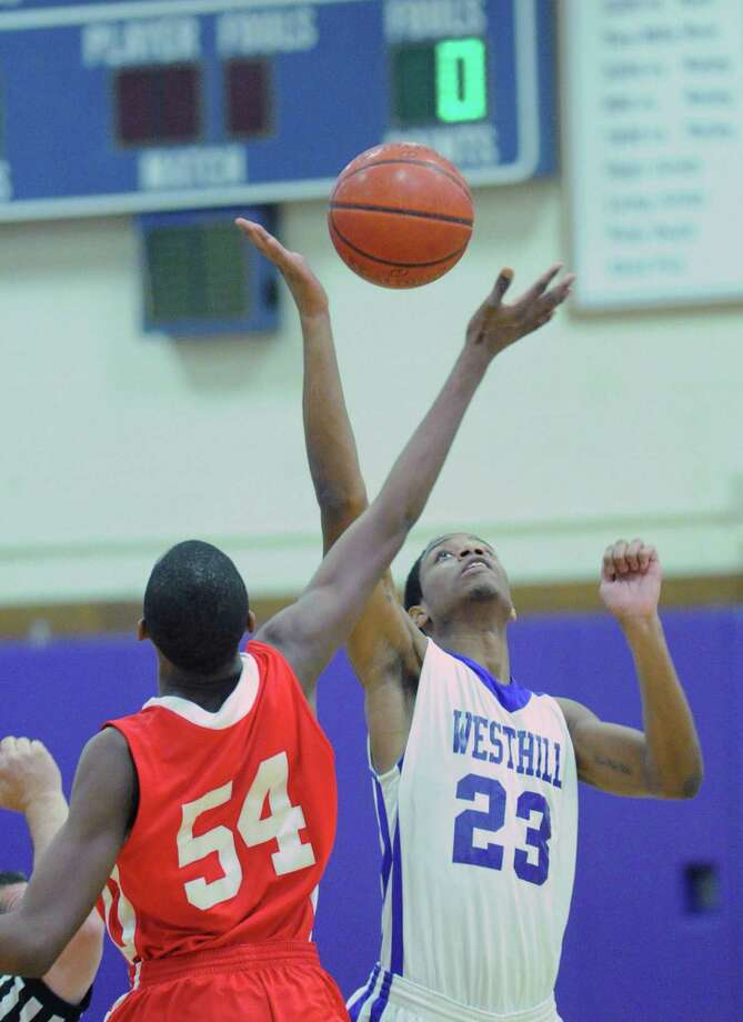 At left, Leonel Hyatt # 54 of Greenwich jumps center against Westhill's Ariel DelaCruz #23, during the boys high school basketball game between Westhill High School and Greenwich High School at Westhill in Stamford, Friday night, Feb. 1, 2013. Photo: Bob Luckey / Greenwich Time