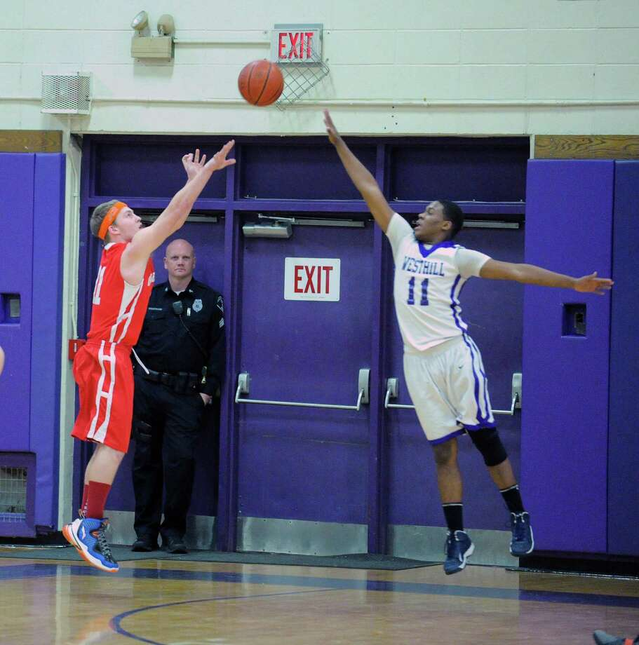 At left, Alex McMurray # 11 of Greenwich shoots while being covered by Guyveson Cassamajor # 11 of Westhill during the boys high school basketball game between Westhill High School and Greenwich High School at Westhill in Stamford, Friday night, Feb. 1, 2013. Photo: Bob Luckey / Greenwich Time