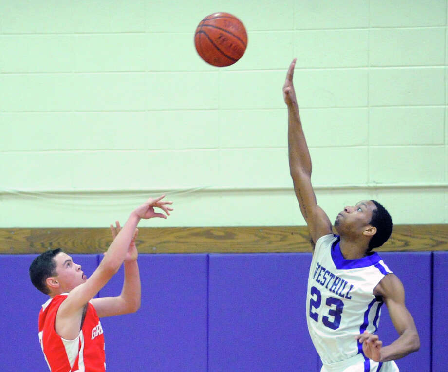 At left, Danny Guise of Greenwich just gets his high arching shot over the out-stretched arm of Westhill's Ariel DelaCruz during the boys high school basketball game between Westhill High School and Greenwich High School at Westhill in Stamford, Friday night, Feb. 1, 2013. Photo: Bob Luckey / Greenwich Time