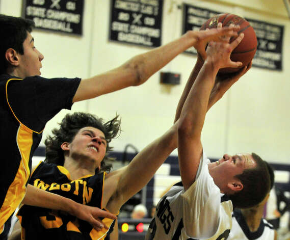 Weston's Matt Folger, left, and Troy Flynn try to block the shot of Mike Scharfenberg, of Immaculate, during their game at Immaculate High School in Danbury on Friday, Feb. 1, 2013. Immaculate won, 63-54. Photo: Jason Rearick / The News-Times