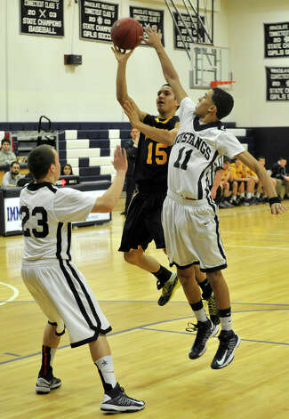 Weston's Asher Lee-Tyson shoots over Immaculate's Mike Scharfenberg, left, and Darel Bowman during their game at Immaculate High School in Danbury on Friday, Feb. 1, 2013. Immaculate won, 63-54. Photo: Jason Rearick / The News-Times