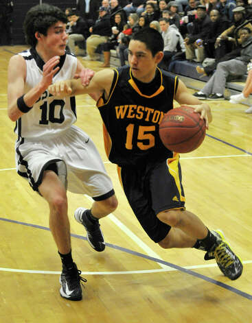 Weston's Asher Lee-Tyson drives around Immaculate's Nick Gerbo during their game at Immaculate High School in Danbury on Friday, Feb. 1, 2013. Immaculate won, 63-54. Photo: Jason Rearick / The News-Times