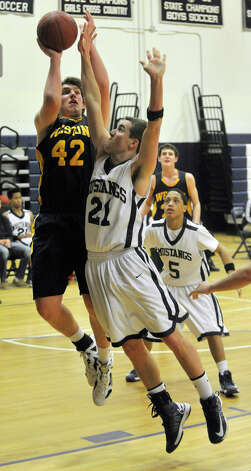 Weston's Grant Limone attempts to shoot over Immaculate's Shane Raymond during their game at Immaculate High School in Danbury on Friday, Feb. 1, 2013. Immaculate won, 63-54. Photo: Jason Rearick / The News-Times