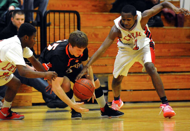 Central's #12 Rickardo Grant, right, attempts to steal the ball away from Ridgefield's #25 Chipper McClelland, during boys basketball action in Bridgeport, Conn. on Friday February 1, 2013. At left is Central's #11 Tyler Ancrum. Photo: Christian Abraham