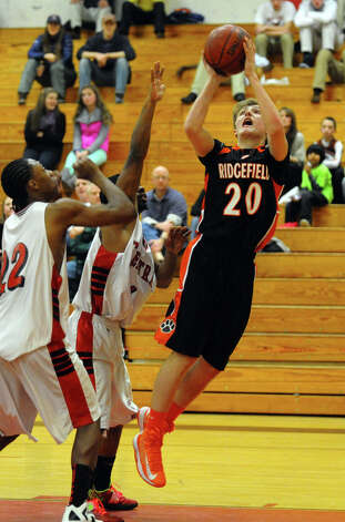 Ridgefield's #20 Matt Brennan tries to lay-up the ball as he is pressured by Central players, during boys basketball action in Bridgeport, Conn. on Friday February 1, 2013. Photo: Christian Abraham / Connecticut Post