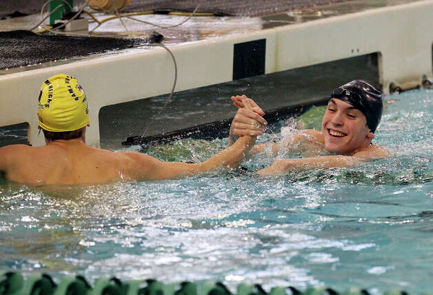 Alamo Heights' Austin Frey (black cap) and teammate Christopher Spears congratulate each other after the 50-yard freestyle at the District 29-4A swim meet at Palo Alto College on Friday, Feb. 1, 2013. Frey took first with a time of 21.89. Photo: Kin Man Hui, Express-News / © 2012 San Antonio Express-News