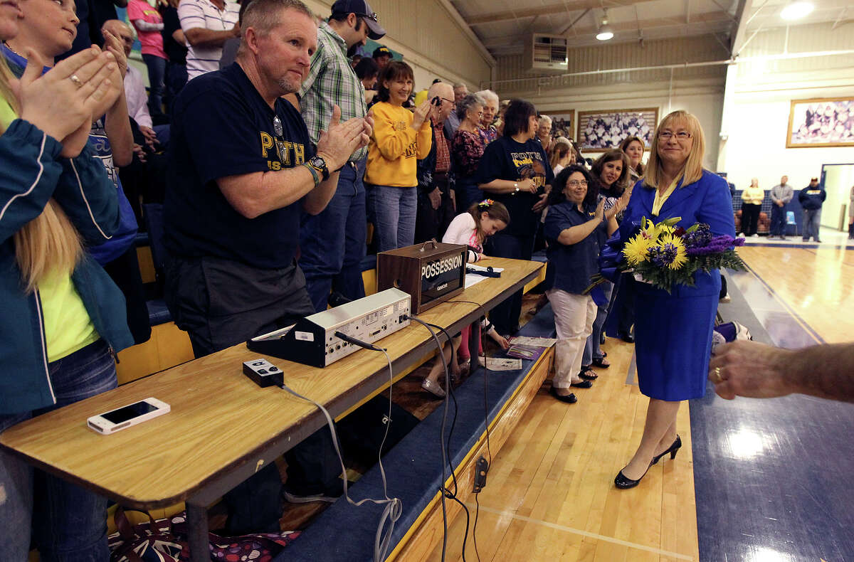 Poth High School girls basketball coach Peggy Hosek (right) receives a standing ovation from the community before her last regular season home game on Friday, Feb. 1, 2013. Hosek is retiring after 32 years as head coach. Hosek has more than 800 wins, two Class 2A state titles and 12 trips to the state tournament as part of her coaching legacy.